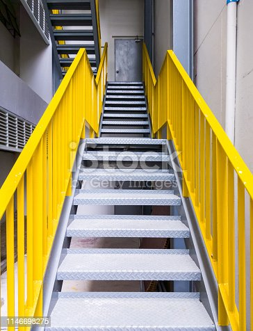 Metal fire escape with the yellow ladder on the office building.