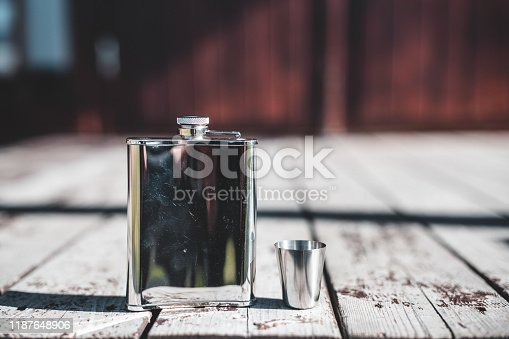 A metal flask on a wooden porch in the sun
