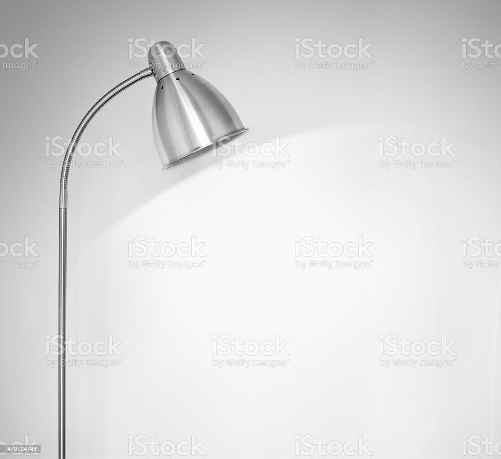 Metal floor lamp standing near white wall stock photo