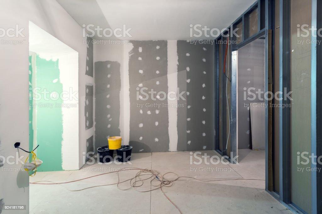Metallrahmen und Gipskartonplatten (Trockenbau) für Gipswände, drei Eimer und elektrischen Leitungen in der Wohnung befindet sich im Aufbau, Umbau, Renovierung, Ausbau, Sanierung und Umbau – Foto