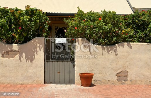Metal gate entryway set in an adobe wall on a bright sunny day.