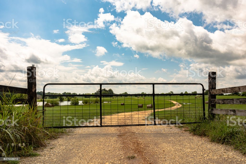 Metal gate on dirt road stock photo