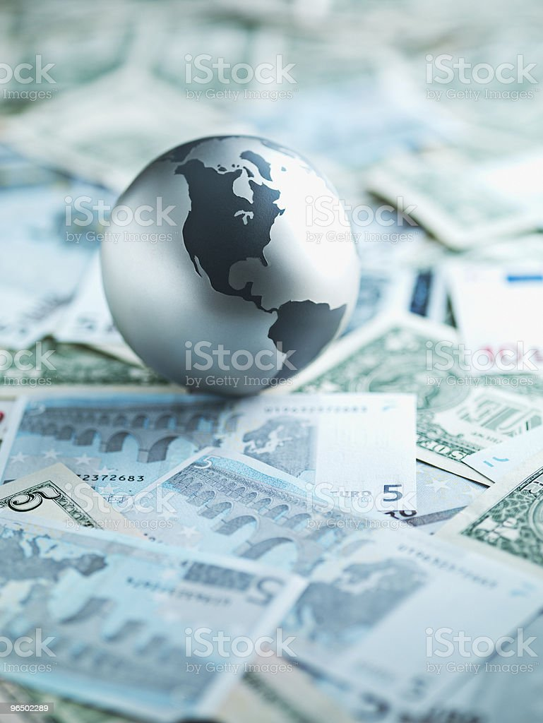 Metal globe resting on paper currency stock photo