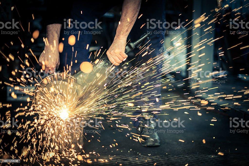 Metal grinding on steel spare part in workshop stock photo
