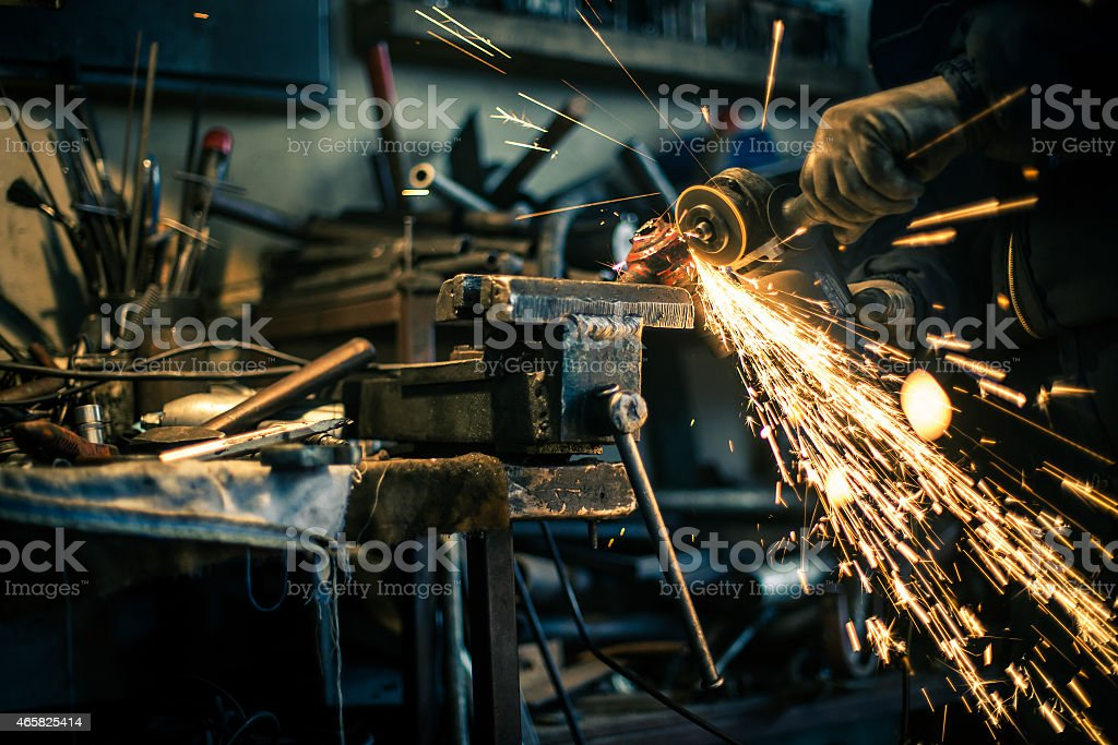 Metal grinding on steel spare part stock photo