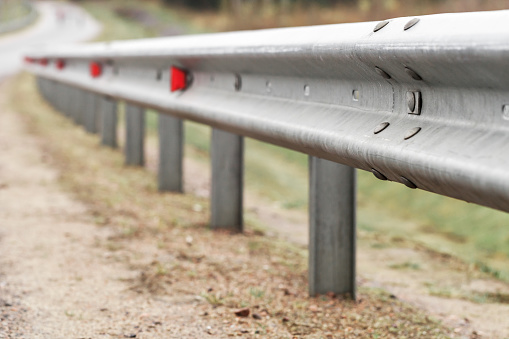 Metal guardrail with retro-reflecting optical units. Highway safety equipment, close-up photo with selective focus