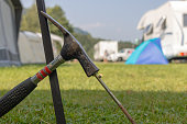 Metal hammer putting a nail-like tent peg out of iron into the grass on the ground.