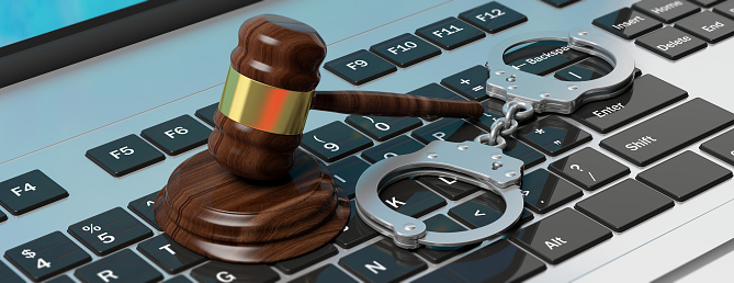 istock Metal handcuffs and judge gavel on computer keyboard, 3d illustration 1056779238