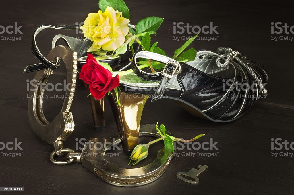 Metal handcuffs and women's shoes. The concept of sexual games stock photo