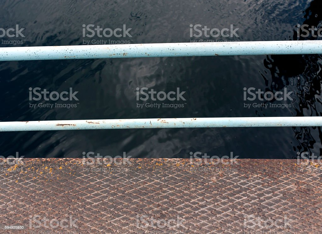 Metal hand-rail and floor against lake side. stock photo