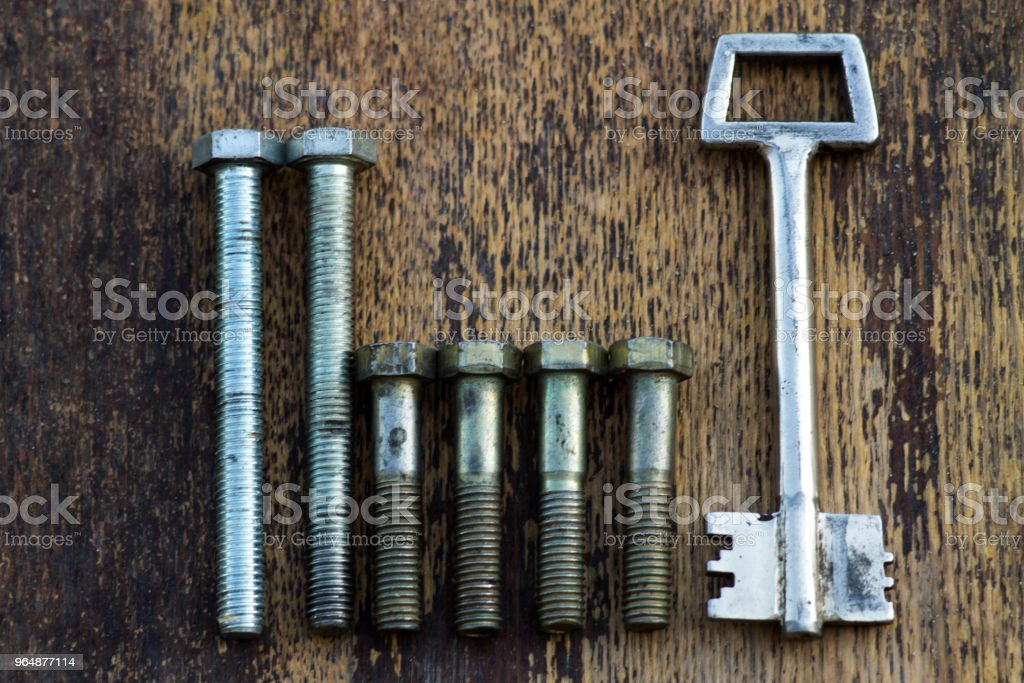 Metal hardware with carvings figures on a wooden background royalty-free stock photo