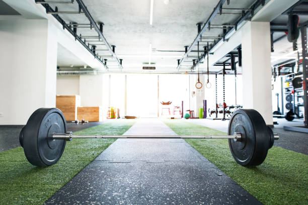 Metal heavy barbell laid on the floor in modern gym. stock photo