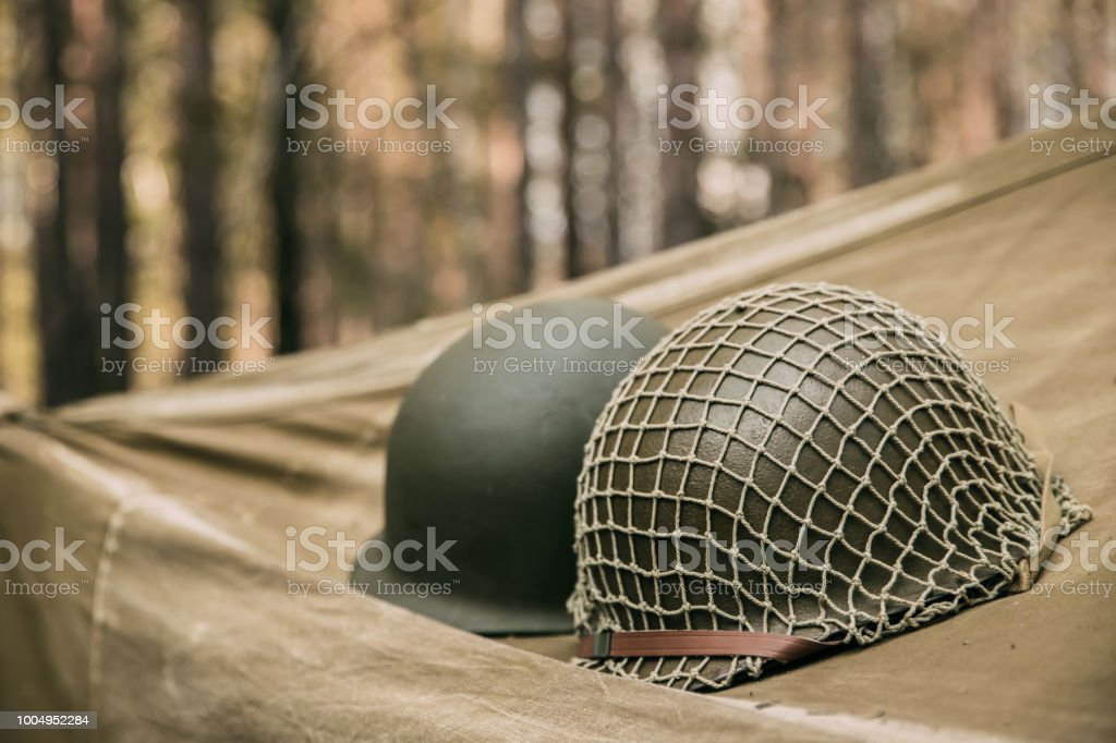 Metal Helmet Of United States Army Infantry Soldier At World War II. Helmet  On Camping Tent In Forest Camp stock photo