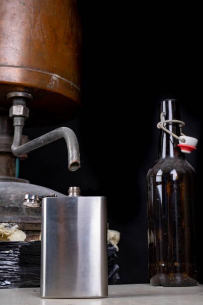 eine metallhüfte an der alkoholdestillationsmaschine. zubehör für menschen, die zu hause alkohol produzieren. schwarzer hintergrund. - whisky test stock-fotos und bilder
