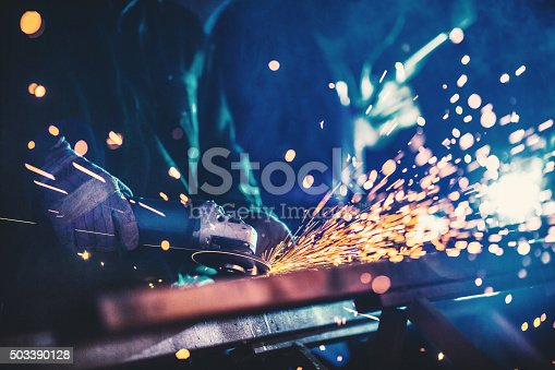 Closeup of heavy industry workers. One of the workers is welding two pieces of metal with arc welding machine. The guy in focus is grinding what his colleague just welded. He's using electric grind stone machine. Deep blue toned shot.