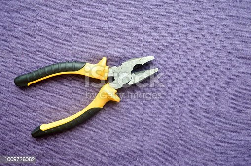 Metal, iron pliers with rubberized yellow-black handles against the background of purple cloth. Bench tools.