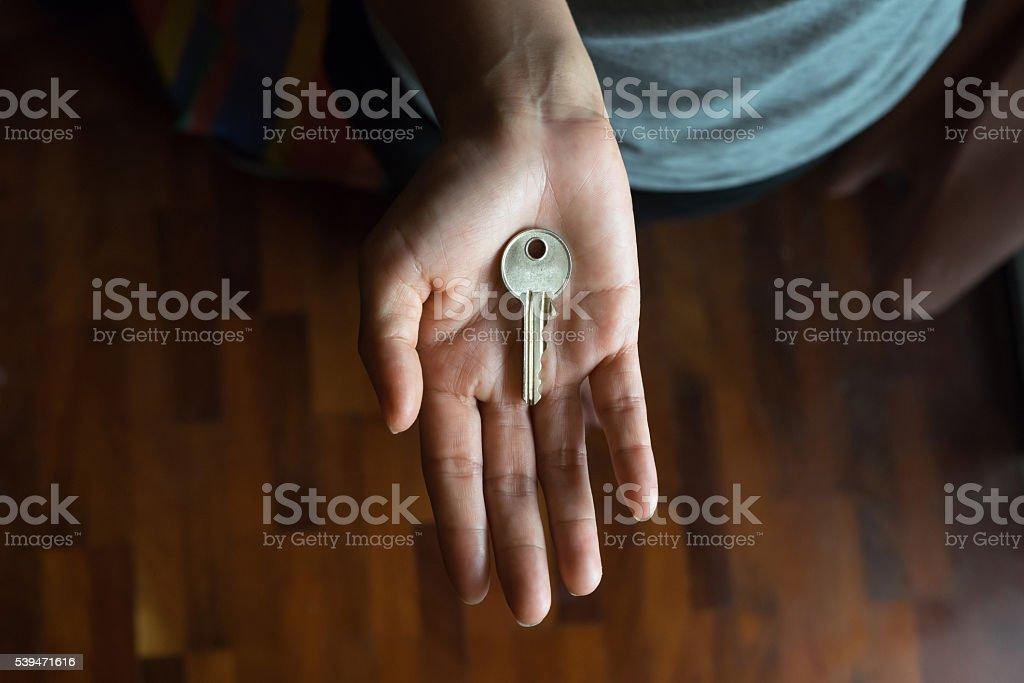 Metal key in female palm stock photo