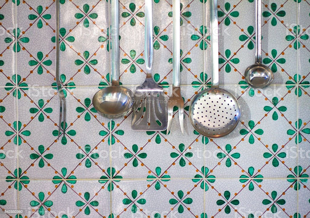 Utensili da cucina in metallo annata appesi contro piastrelle