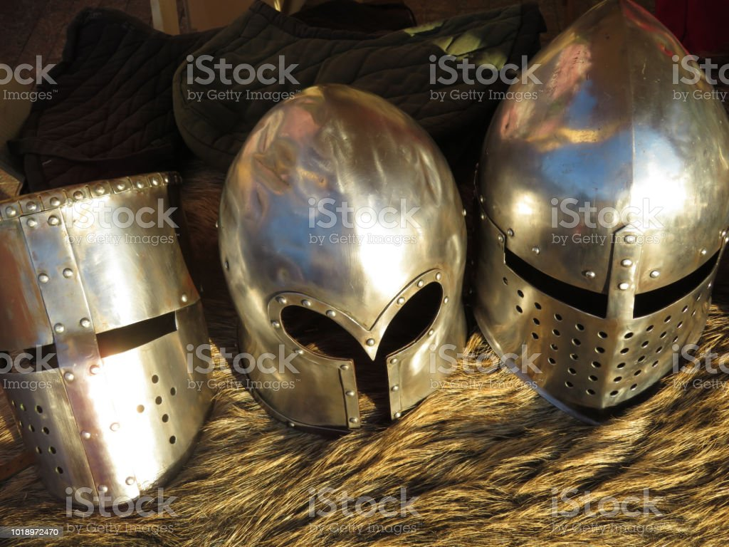 Metal knightly helmets on a bearskin rug stock photo
