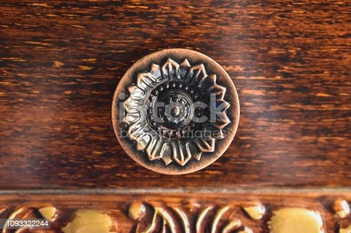 Circular metal knob with geometric flower design engraved on it, with a rich warm wood background, on a chest of drawers.