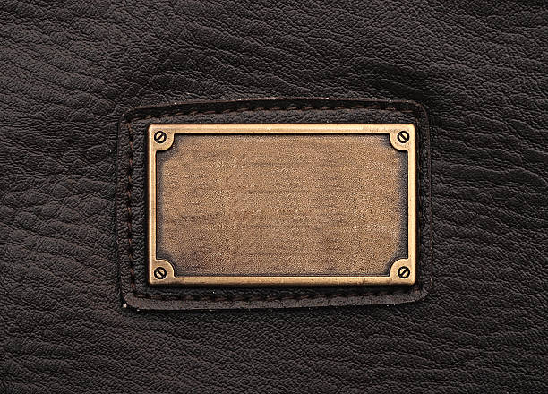 metal label on old black leather background stock photo