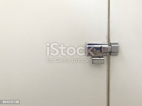 Metal latch in bathroom door stall with copy space used for bathroom product