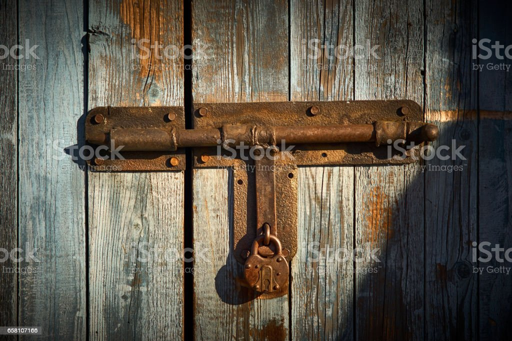 metal latch with padlock on the wooden door royalty-free stock photo