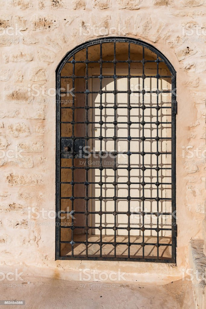 A metal lattice in front of the gates set in a sandstone wall of the fort stock photo