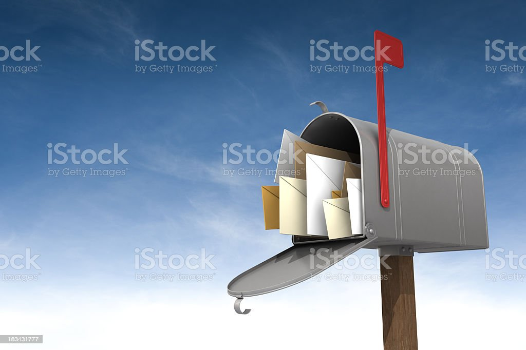 A metal mailbox filled with letters against the sky stock photo