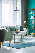 Metal marble table with decorative balls in bowl in green living room interior with light grey sofa and windows with curtains