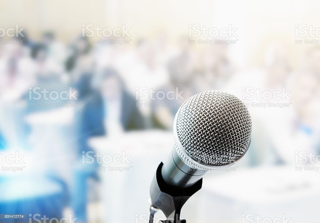 Metal microphone with out-of-focus people in background stock photo