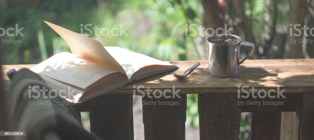 Metal mug, book and chair on a wooden terrace stock photo