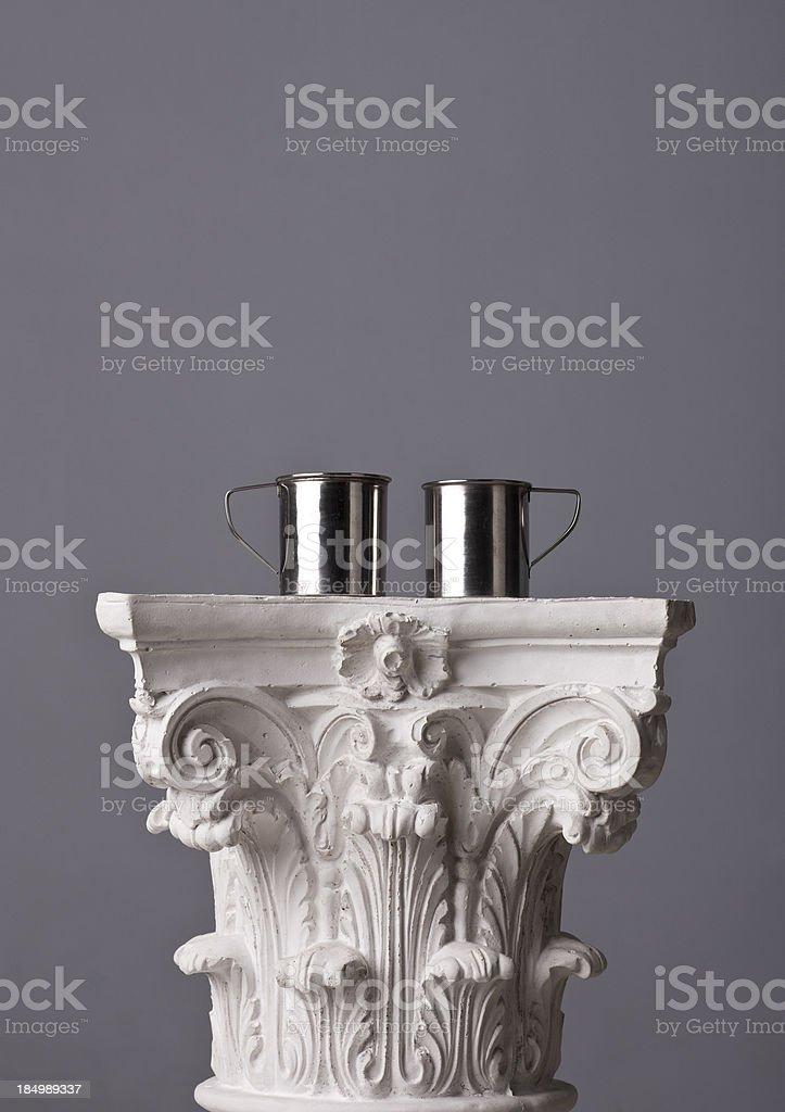 metal mugs on a corinthian capital royalty-free stock photo