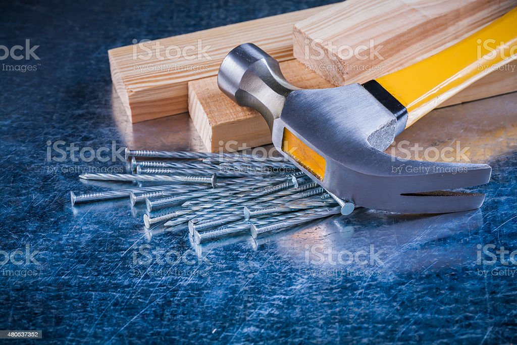 Metal nails claw hammer and wooden studs on scratched metallic stock photo