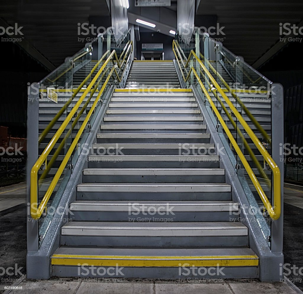 Metal outdoor stairs with yellow handrails and glass sides stock photo