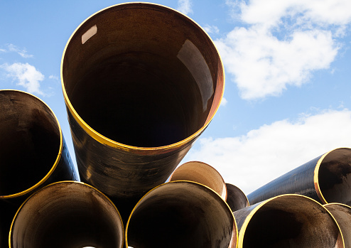 Stack of new metal pipes with yellow-painted edges. Industrial material.