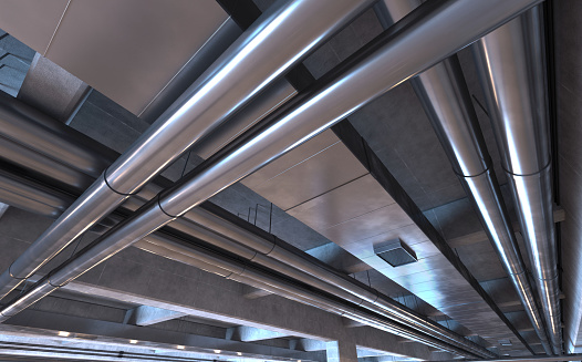 Pipes, tubes and air ducts on a garage ceiling or underground space. Metal, aluminum and steel equipment. Engineering details. Modern industrial background with dim illumination. Digitally generated image.