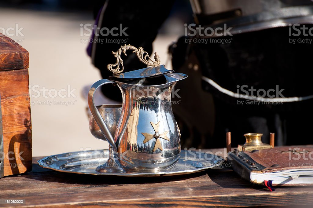 Metal pitcher with maltese cross stock photo