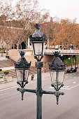 Metal pole with street lamps near the roadway. High quality photo