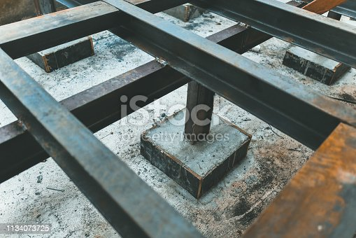 Metal poles on concrete bases. Foundation construction site making reinforcement metal framework for pouring concrete to home building.