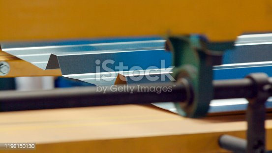 The industrial device for sheet metal bending by high precision metal sheet bending machine in factory. Close up. Selective focus.