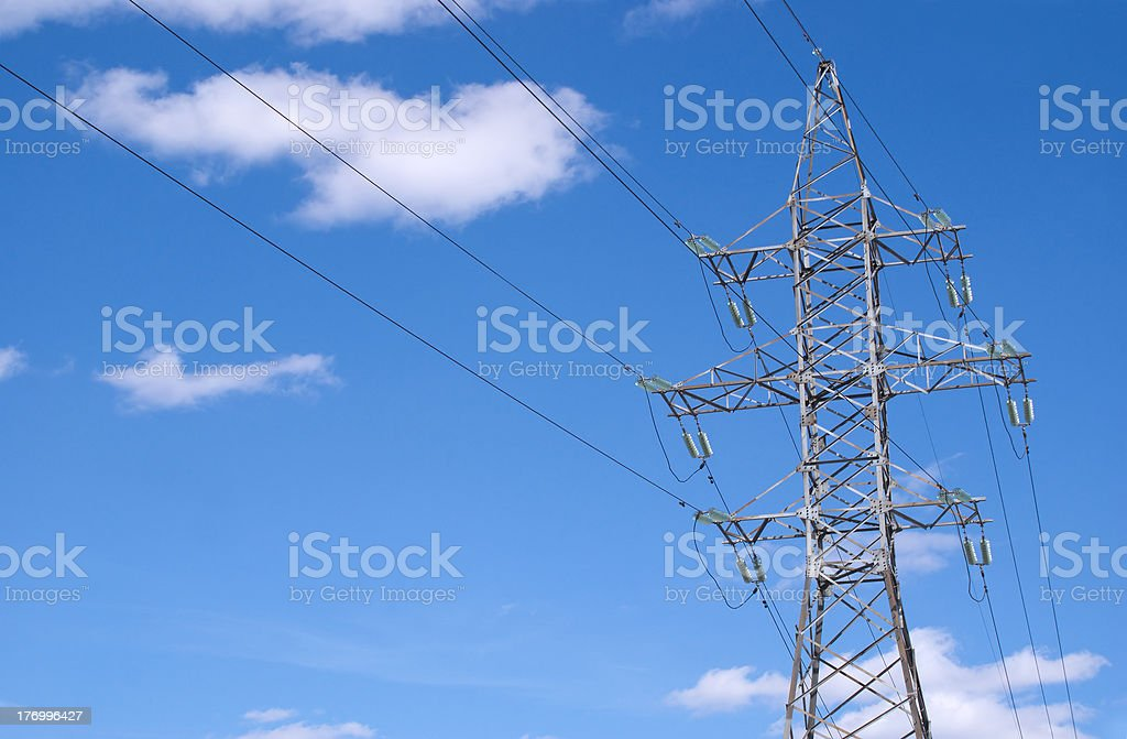 Metal prop and high-voltage power line over blue sky stock photo