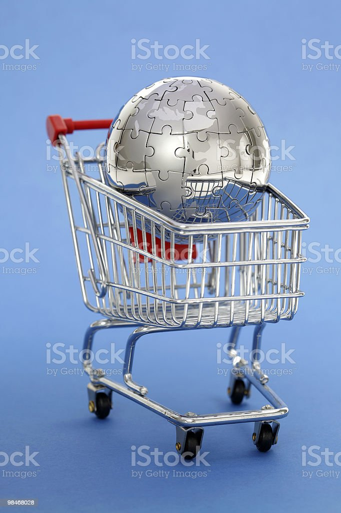Metal puzzle globe with shopping cart on blue background royalty-free stock photo