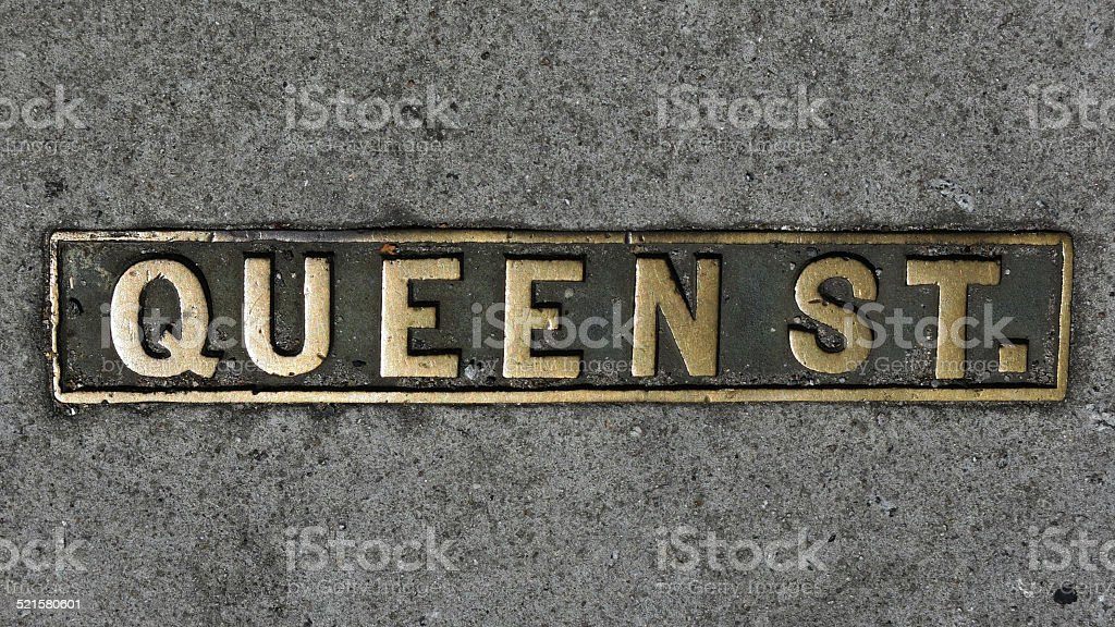 Metal Queen Street Plaque Sign in Gold on Road stock photo