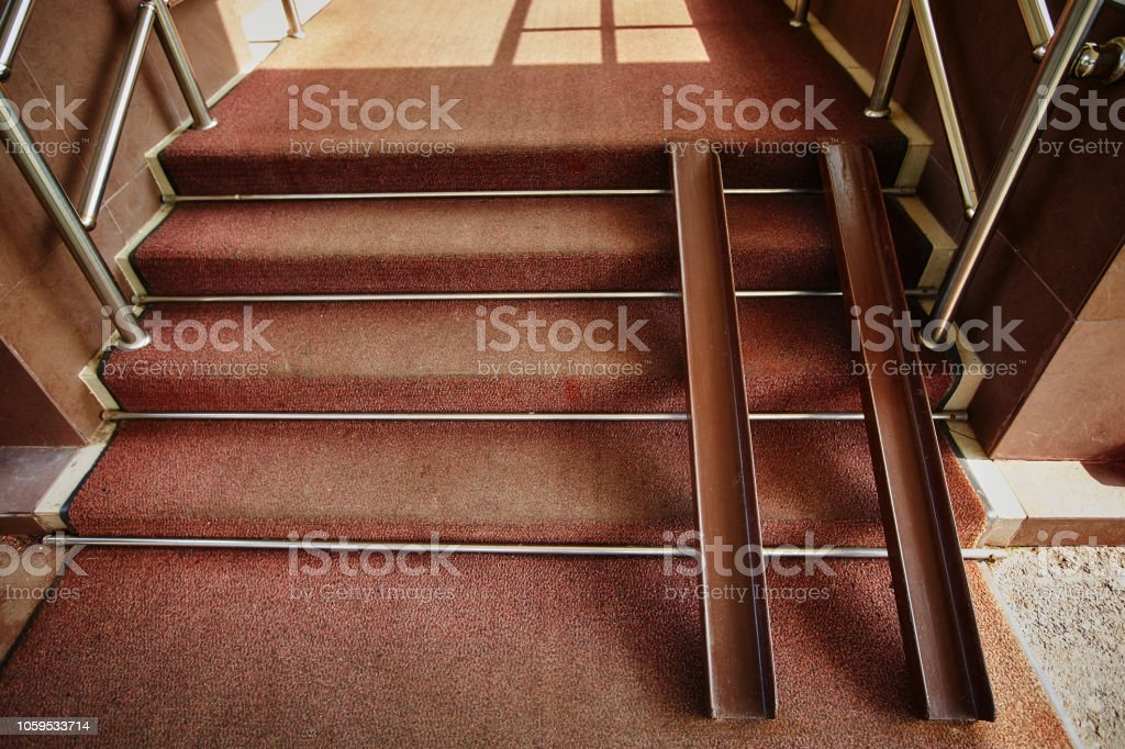 Metal rails for wheelchairs in the doorway of the store. Ramp for...
