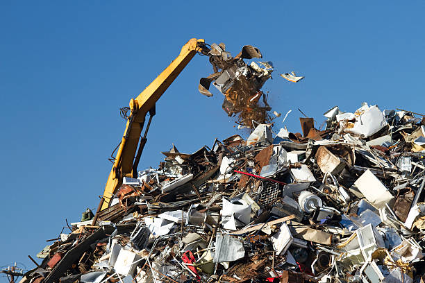 Metal Recycling Junkyard, Blue Sky, With Crane Throwing Trash stock photo