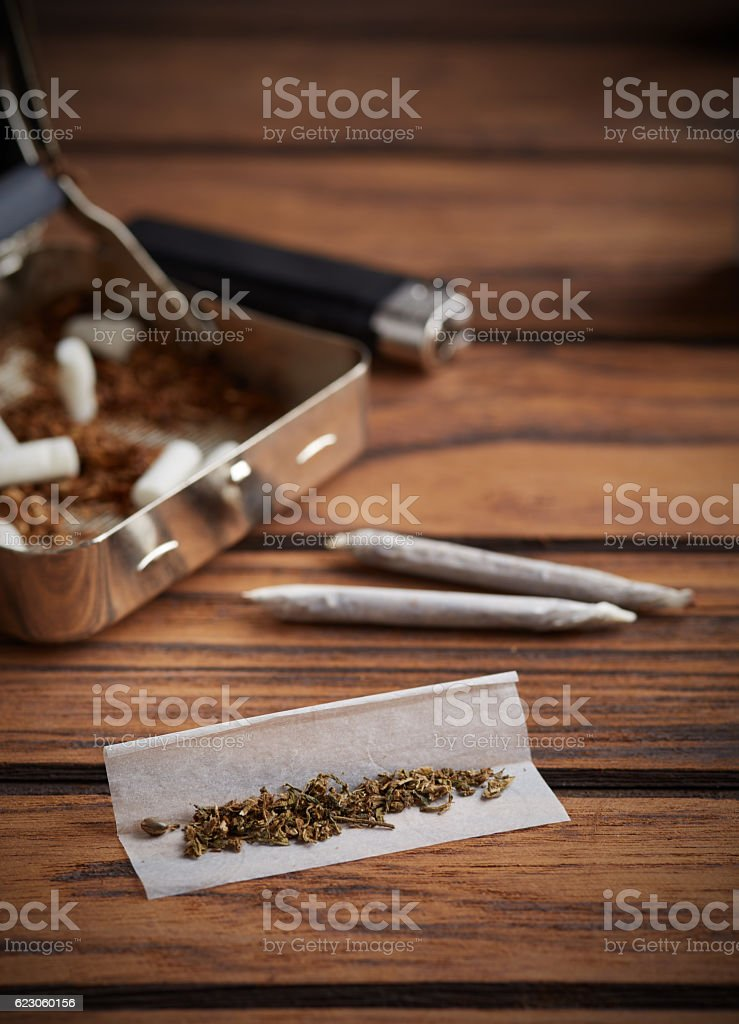 Metal rolling machine with some filters for rolled marijuana joint stock photo