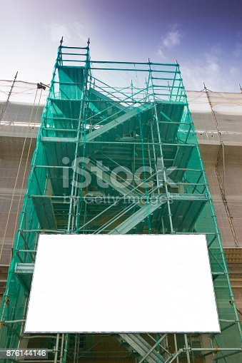 istock Metal scaffolding, with prefabricated components and blank billboard, to work on the facade for the renovation of the plaster wall 876144146