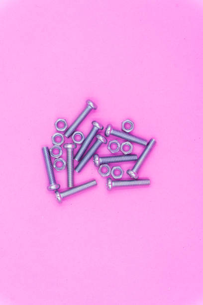 Metal Screws and Nuts on Pink pastel background stock photo