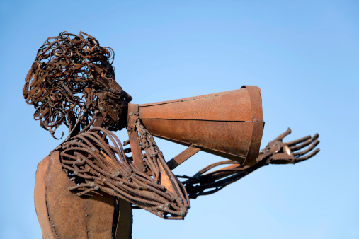 Metal sculpture shooting a movie scene with a megaphone